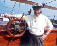 Gene Savoy standing with captains wheel on Feathered Serpent III