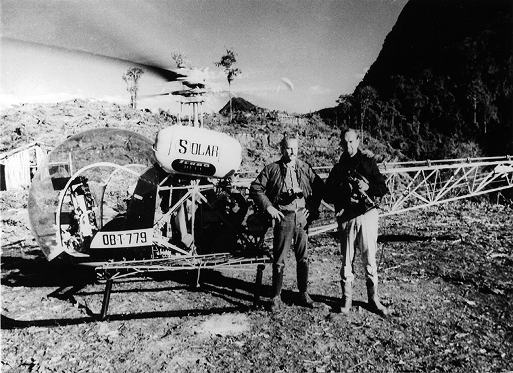 Gene Savoy Sr. in front of helicopter with pilot